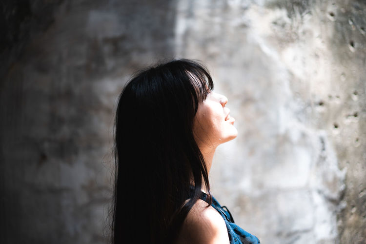 Side view of smiling mid adult woman looking away by wall