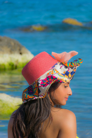 Rear View Of Woman Wearing Hat At Beach