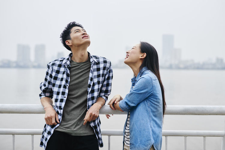Smiling couple standing by railing against sky