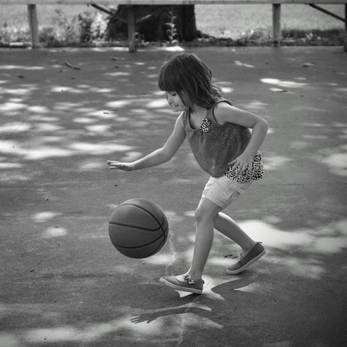 Girl playing with ball on road