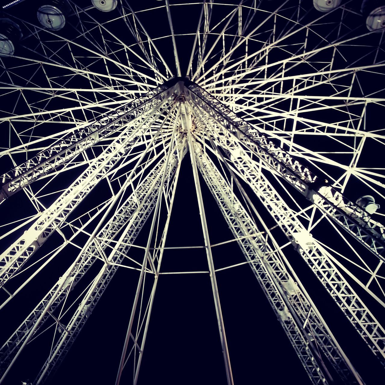 low angle view, amusement park, arts culture and entertainment, night, amusement park ride, ferris wheel, no people, built structure, architecture, big wheel, clear sky, illuminated, outdoors, sky
