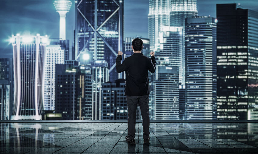 Rear view of businessman standing in buildings against sky