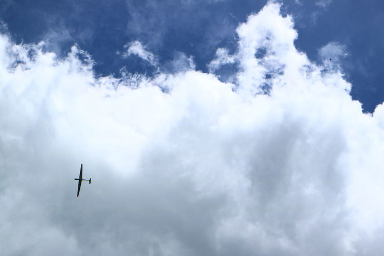 Low angle view of glider flying in cloudy sky