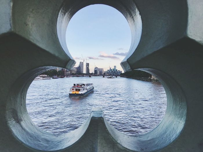 Boats sailing in river seen through arch