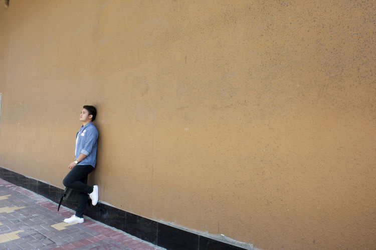 Young Man Leaning On Orange Wall