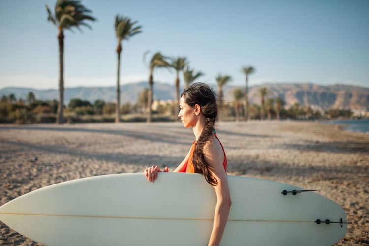 Side view of woman carrying surfboard while walking at beach