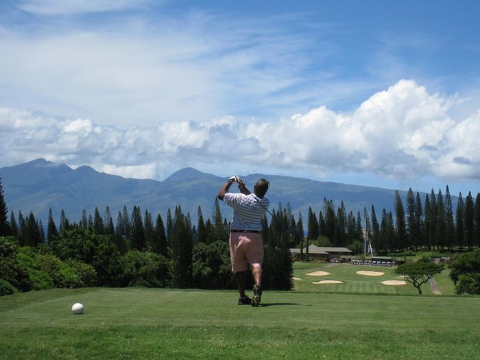 Full length rear view of man playing golf against sky during sunny day