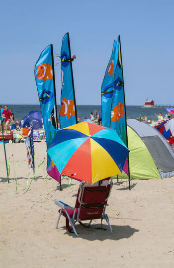 May 22 2016 Grand haven Michigan; kites fly on the beach at the Grand haven kite festival in the USA, and this beach chair with umbrella is the best seat in the house Beach Chair Umbrella Best Seat In The House BIG Event Fun Grand Haven Kites Lake Michigan Michigan Toys USA Beach Clear Sky Colorful Day Editorial  Festival Flight Flying Go Fly A Kite Nature Outdoors Sand Sky Water