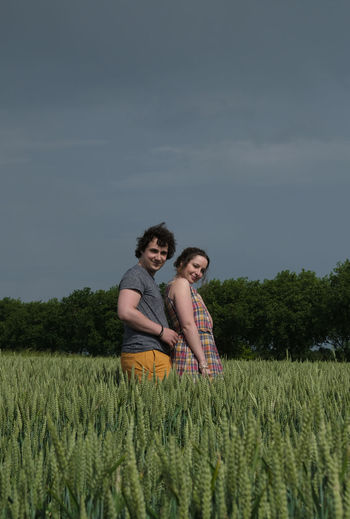 Side view of friends standing amidst plants on field against sky
