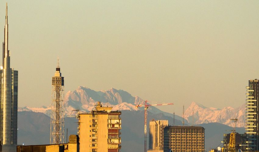 Buildings by mountains against clear sky
