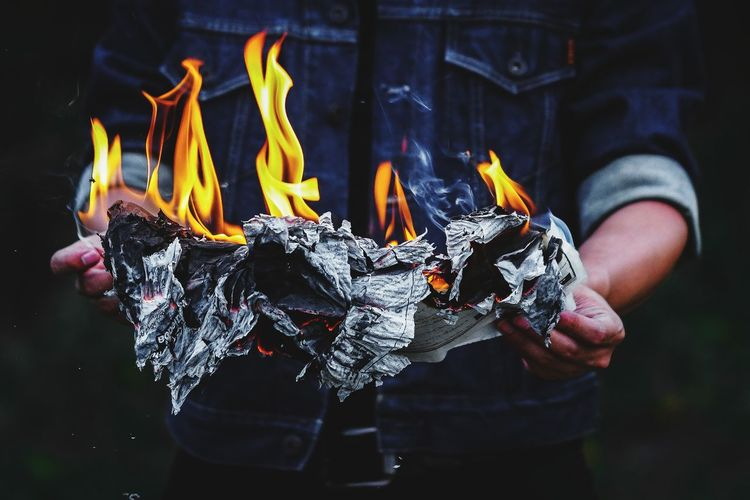 Midsection of man holding burning paper