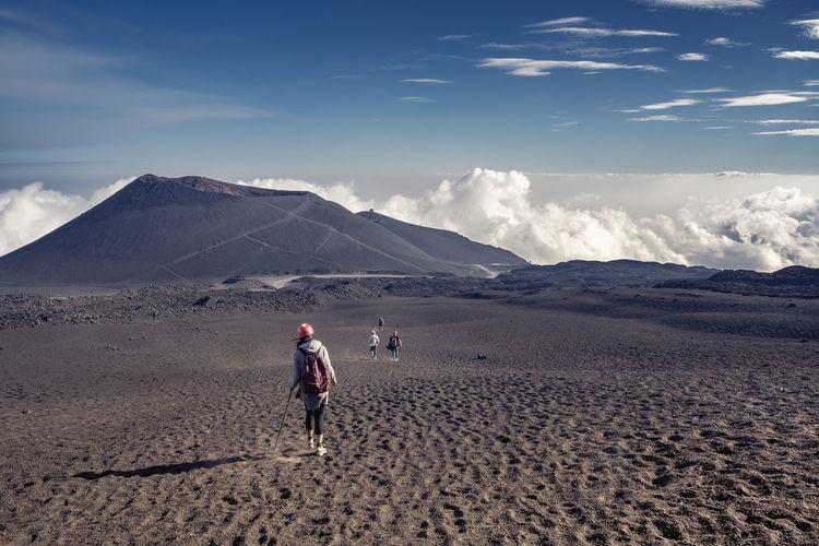 Rear view of men walking on land against sky