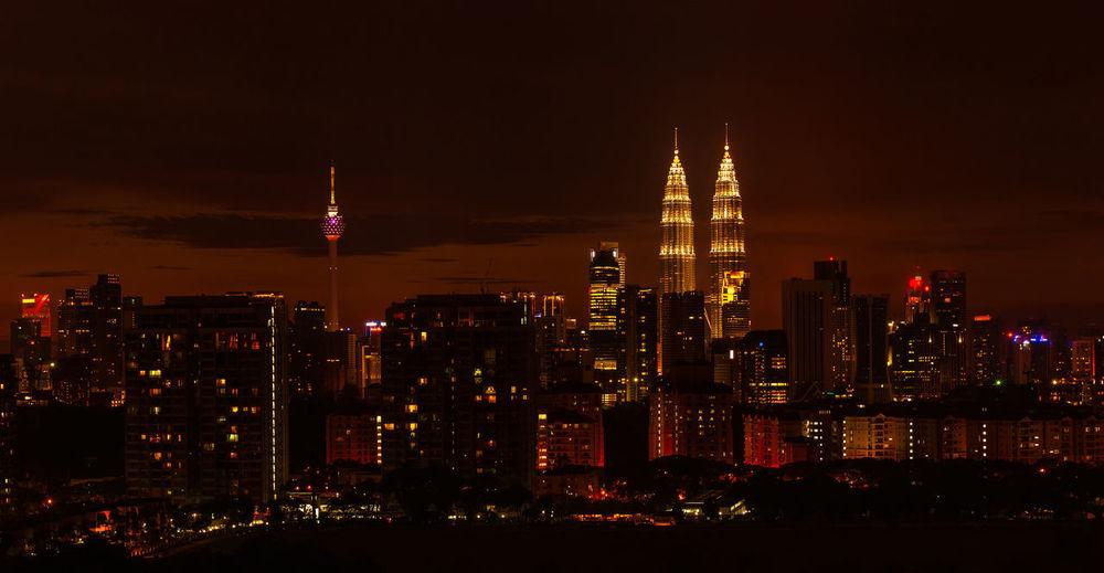 Illuminated petronas towers and menara kuala lumpur tower amidst buildings at night