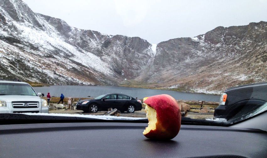Close-up of eaten apple on dashboard against lake by mountains during winter