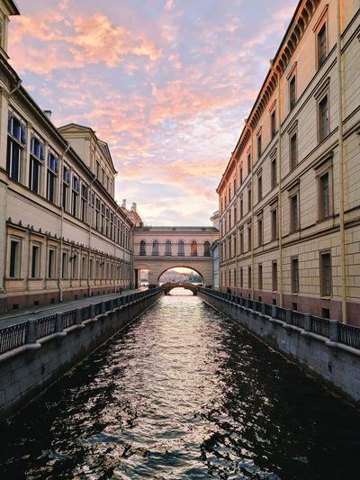 Canal amidst buildings in city against sky during sunset