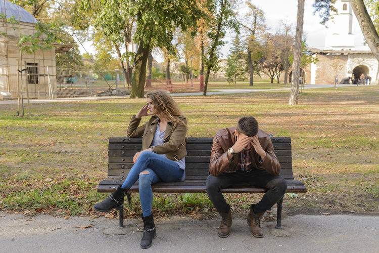 Couple having a relationship problem Adult Bench Casual Clothing Couple - Relationship Day Emotion Full Length Hairstyle Nature Outdoors Park Park - Man Made Space Park Bench People Plant Real People Relaxation Sadness Seat Sitting Teenager Togetherness Tree Two People Women