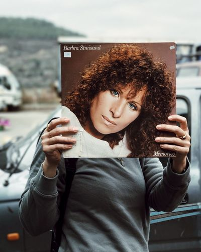 The other side Lifestyles Transportation One Person Wireless Technology Holding Mobile Phone Curly Hair Communication Car Only Women Front View Portable Information Device Standing Music Portrait מייאייפון7 מייסטריט מייתרשיחא Adapted To The City