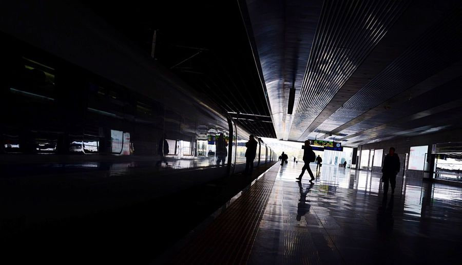 Silhouette people walking in subway station