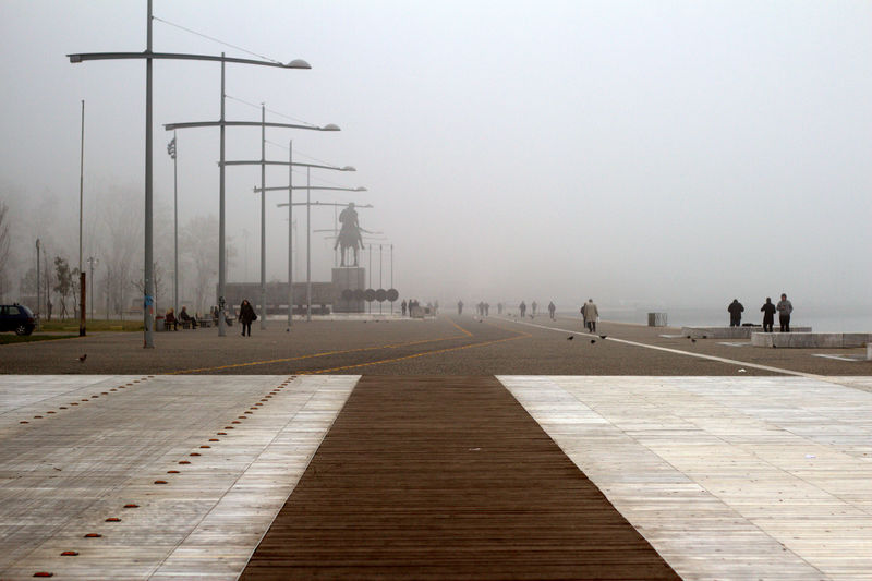 People walk at Thessaloniki seafront during a foggy morning. Light Pole Light Post Misty Thessaloniki Urban Architecture Urban Geometry Architecture Day Fog Foggy Foggy Morning Outdoors Real People Salonica Salonika Seafront Selanik Sky Travel Destinations Urban Walkway