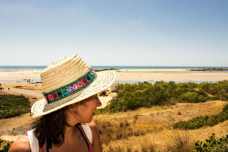 Praia de Cacela Velha. Beach Blue Casual Clothing Clear Sky Day Hat Headshot Horizon Over Water Knit Hat Leisure Activity Lifestyles Long Hair Person Rear View Scenics Sea Sky Summer Vacations Water Young Adult Young Women