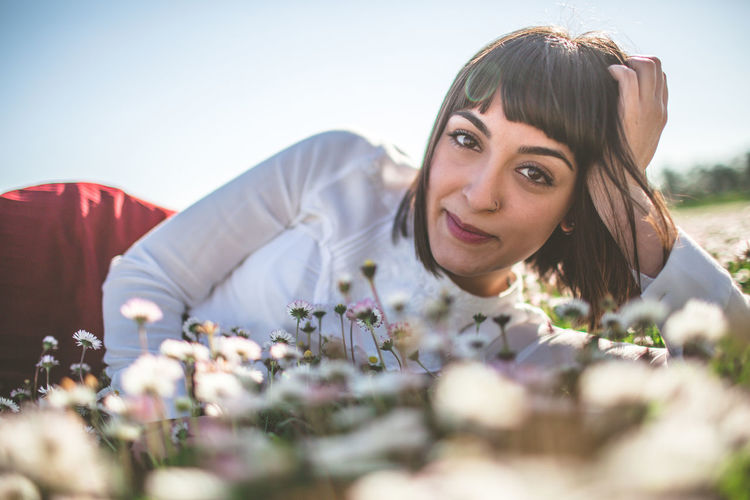 Portrait of happy young woman relaxing on flowers field