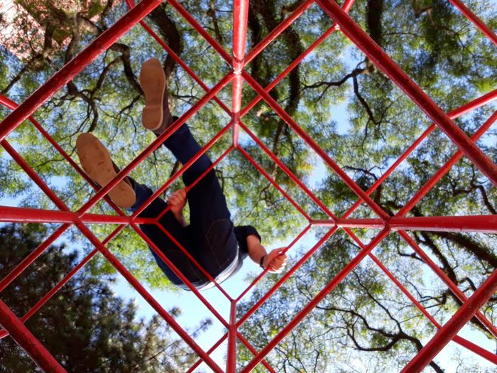 Low Angle View Of Man On Metallic Structure At Park