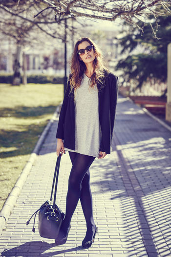 Portrait Of Young Woman Holding Handbag While Standing On Footpath