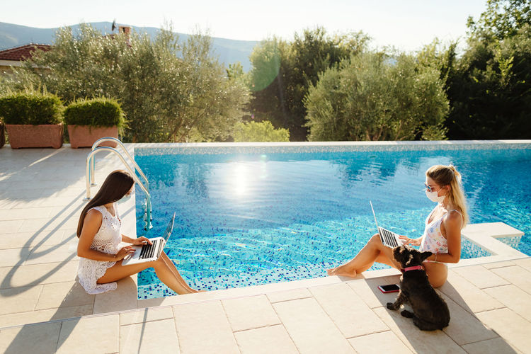 High angle view of women using laptop while sitting by swimming pool with dog