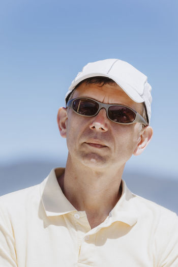 Man wearing sunglasses and cap against clear sky