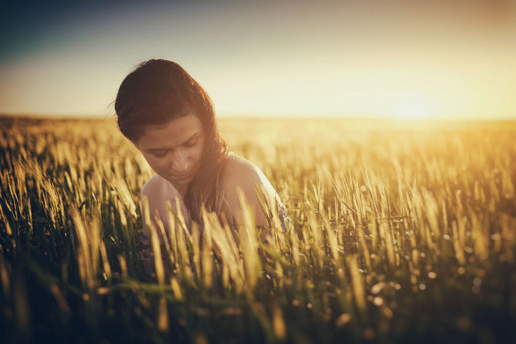 Woman Sitting Amidst Plants On Field Against Sky During Sunset