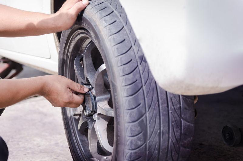 Cropped Hands Of Man Repairing Car Wheel