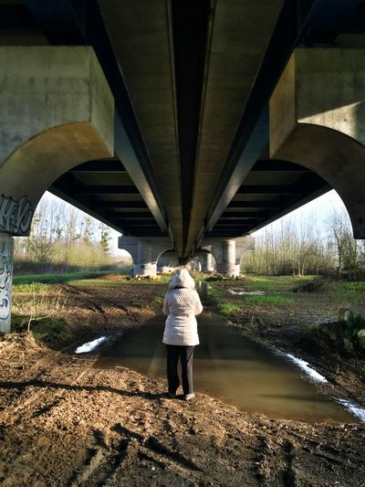 Rear view of woman standing under bridge