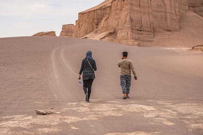 Rear view of people walking on rock