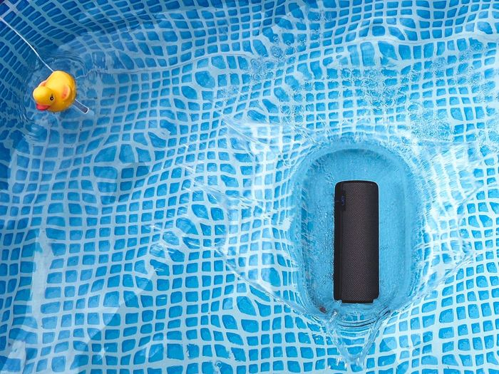 Rubber duck and speaker floating in swimming pool
