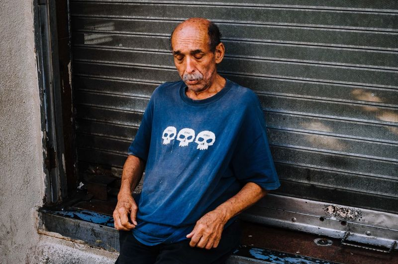 Zero The Art Of Street Photography One Person Adult Shutter Portrait Front View Social Issues Males  Standing Men Casual Clothing Architecture Blue Looking At Camera Waist Up Mature Adult Three Quarter Length Emotion Real People Day Streetphotography Street Photography EyeEm Best Shots EyeEm Selects The Street Photographer - 2019 EyeEm Awards
