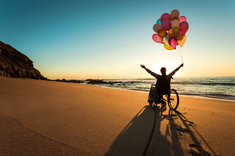 Silhouette mid adult woman with arms raised holding colorful balloons while sitting on wheelchair at beach during sunset