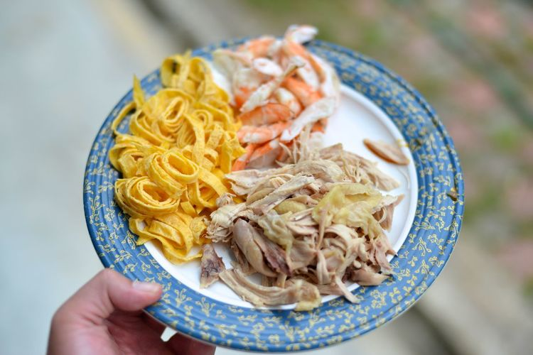 Close-up of hand holding laksa ingredients in plate