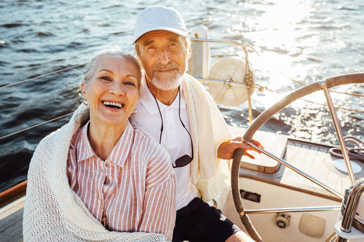 Portrait of smiling couple sitting on sailboat in sea