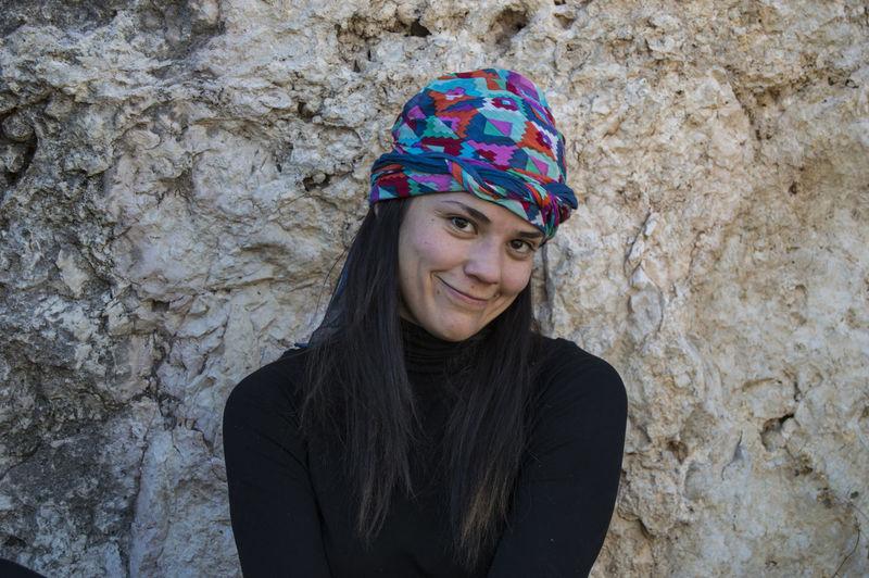 Portrait of smiling woman against rock