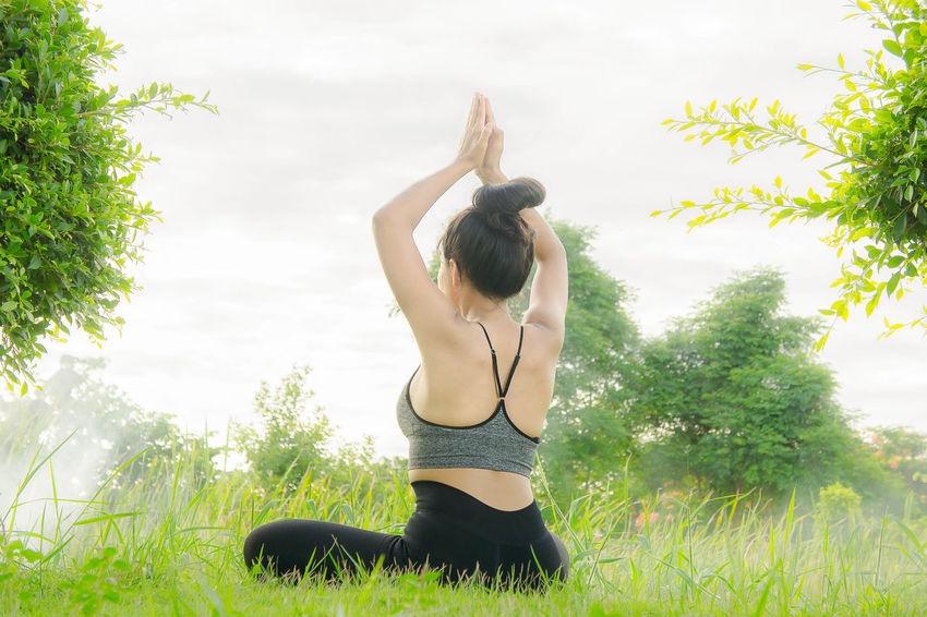 yoga in the nature Arms Raised Balance Concentration Day Exercising Flexibility Grass Growth Healthy Lifestyle Leisure Activity Lifestyles Nature One Person Outdoors Practicing Real People Sky Sports Clothing Tree Yoga Young Adult Young Women