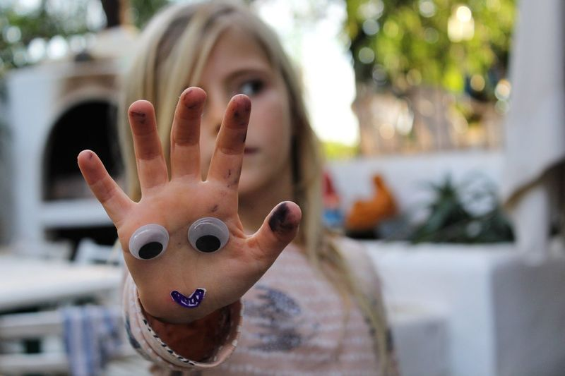 Girl looking away while showing hand with googly eyes