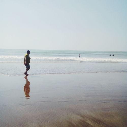 Full Length Of Senior Woman Walking On Shore At Beach