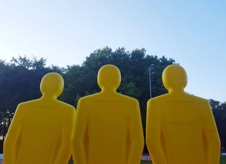 AI Now Statue Low Angle View In A Row Yellow Majestic Respect Strangers Fear Figure Dummy Blank Hollow Fake Confrontation Face-Off Clear Sky Total Strangers Unreal Pseudo Barrier Blockade Paint The Town Yellow