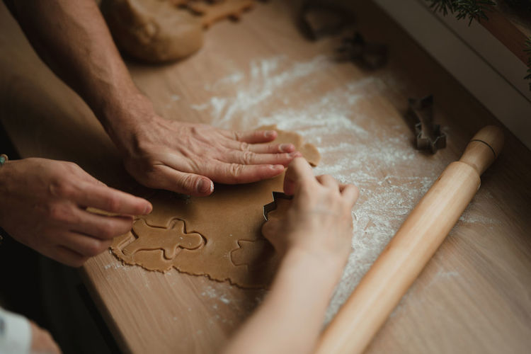High angle view of man hands making gingerbread from dough