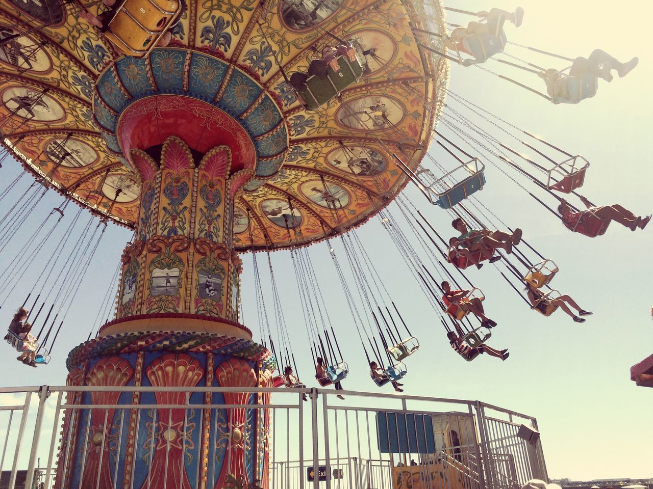 Low angle view of people enjoying carousel against sky
