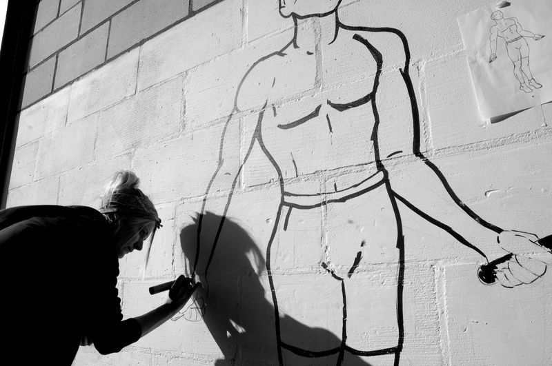 Wall - Building Feature Graffiti Real People Art And Craft Built Structure Creativity People Shadow Lifestyles City Architecture Wall Day Holding Communication Waist Up Standing Sunlight Building Exterior