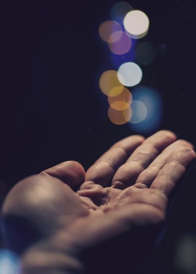 Cropped image of hand against illuminated lights at night