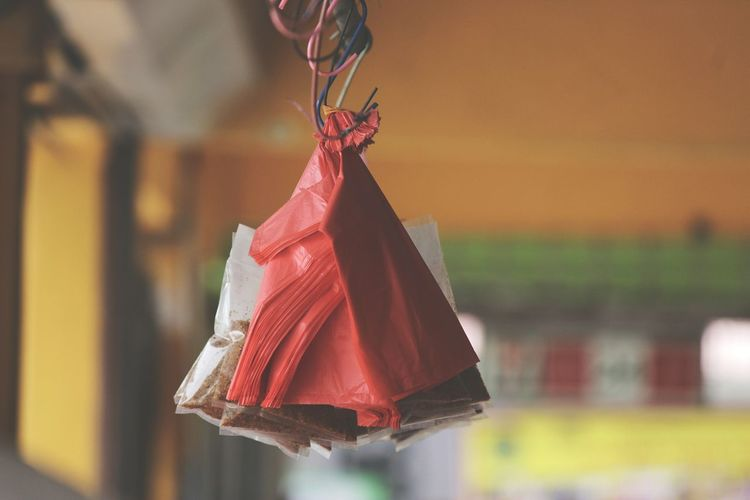 Close-Up Of Plastic Bags And Food Hanging From Hook In Store