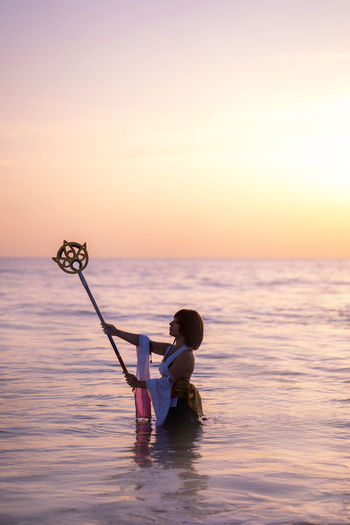 Young woman holding wand in sea during sunset