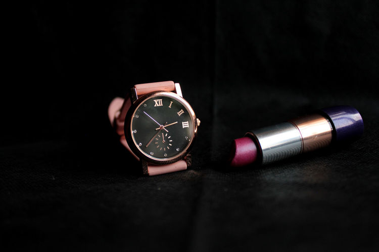 Close-up of wristwatch and lipstick against black background